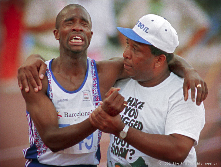 "Derek Redmond of Great Britain is in agony as he is helped to the finish line by his father, Jim, after tearing his hamstring muscle in the semi-finals of the men's 400 meter run. Redmond collapsed about half way through the race with the injury, but got up, determined to finish despite the pain. His father came out of the stands and onto the track to help his son. Redmond initially tried to push him away, not realizing who he was, but then heard a familiar voice. ""Derek, it's me"" his father said. Redmond told his father ""I've got to finish this race."" His father said ""If you're gonna finish the race, we'll finish it together."" With his father's help, Redmond made it to the finish line. Redmond, a brilliant runner whose career was plagued by injuries, had previously suffered a similar fate during qualifying for the 400 meter race in the Summer Olympics in Seoul, South Korea. In a qualifying heat for the 400 meter race, he pulled an Achilles tendon, an injury that led to five surgeries. Later, watching a video of that 1992 Olympic race, Redmond said ""I don't think I've ever cried so much in my life. It's more embarrassing than anything else--men don't cry."" Photo by Jerry Lodriguss / The Philadelphia Inquirer"